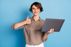 Portrait of positive nice girl hold laptop show thumb up wear checkered isolated on blue color background