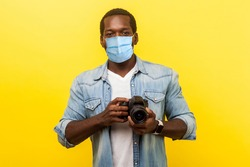 Portrait of positive photographer, man with medical mask holding professional digital dslr camera and looking with toothy smile, enjoying his job. indoor studio shot isolated on yellow background