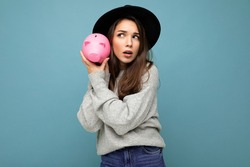 Portrait of positive shocked amazed young beautiful pretty brunette woman wearing gray pullover and black hat isolated over blue background with free space and holding pink piggy box. Money box