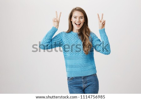 Portrait of positive smiling caucasian female raising hands while showing air quote gesture or victory sign, being in good mood and standing against gray background. Girl indicating irony in her words stock photo