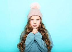 Portrait of positive smiling child with blond wavy hair and winter hat. Happy beautiful pretty girl look at camera and smile. Close up.