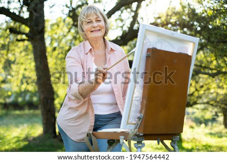 Fototapete Portrait of positive talented middle aged woman artist standing in front of easel outdoors in the green park, holding brush, working on a picture. Creativity, inspiration, art and painting concept