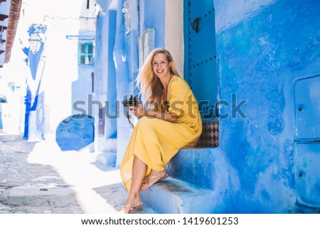 Portrait of positive woman using retro equipment while resting near blue building of Chaouen enjoying summer trip for visit ancient city, cheerful Caucasian tourist with vintage camera outdoors