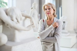 Portrait of positive woman visitor near sculpture in the historical museum