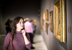 Portrait of positive young girl attentively looking at paintings in art museum