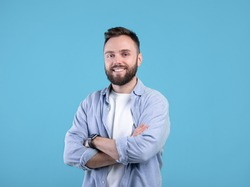 Portrait of positive young guy posing with crossed arms and smiling at camera on blue studio background