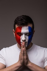 Portrait of Pray France football fan in game  of France national  team with close eyes. European football fans concept.
