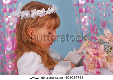 portrait of praying girl going to the first holy communion and posing in studio