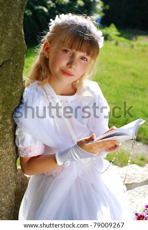 portrait of praying girl in white dress and  wreath,going to the first holy communion posing in park