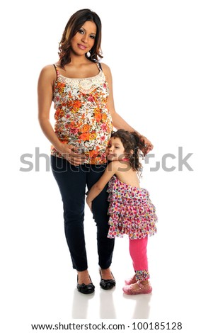 Portrait of pregnant Hispanic mother with daughter standing over white background