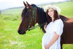 Portrait of pregnant woman in wreath near horse