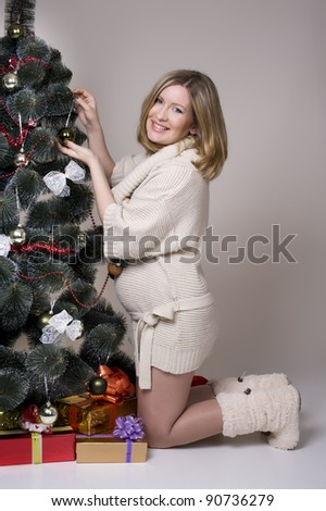 portrait of pregnant woman standing by Christmas tree