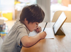 Portrait of preschool kid using tablet for his homework,Soft focus of Child doing homework by using digital tablet searching information on internet,E-learning or Home schooling education concept
