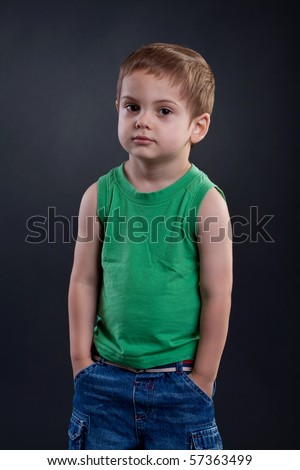 Portrait of preschoold boy posing green shirt and jeans,standing with his hands in his pockets