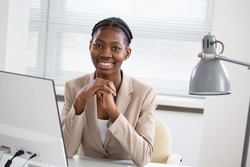 Portrait of pretty africanamerican business woman looking at camera at workplace in an office