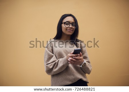 Portrait of pretty afro american girl in casual outfit sending messages on mobile chatting online with friend standing on promotional background, charming dark-skinned woman checking email on phone