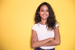 portrait of pretty asian girl smiling with arm crossed on yellow background