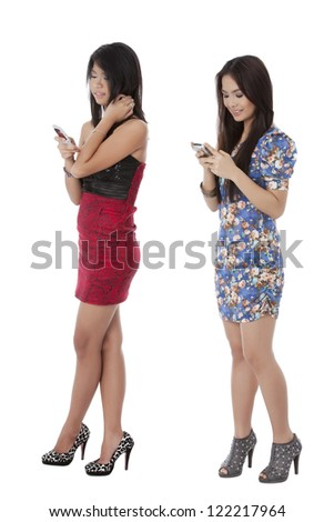 Portrait of pretty Asian models busy looking at their cellular phone isolated on