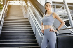 Portrait of pretty asian woman Standing on floor of city street after running. Female athlete runner resting, workout outdoors on fresh air, jogger take break, wearing sports outfit.