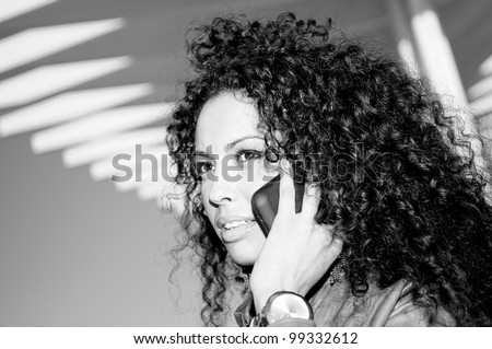 Portrait of pretty black woman, with afro hairstyle, in urban background talking on phone