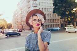 Portrait of pretty blonde girl with short hair posing to the camera on the street in city. She wears gray checkered  dress, glasses, hat and has purple lips.
