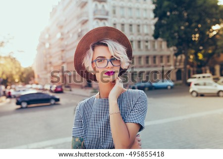 Portrait of pretty blonde girl with short hair posing to the camera on the street in city. She wears gray checkered  dress, glasses, hat and has purple lips. #495855418