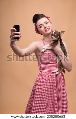 Portrait of pretty brunette  girl in rose dress and red headband in retro style  with Chihuahua doing selfie smiling looking at phone  waist up #238280653