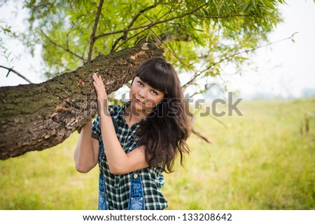 Portrait of pretty brunette holding the trunk