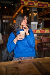 Portrait of pretty brunette in a cafe. Enjoying latte and looking into distance.