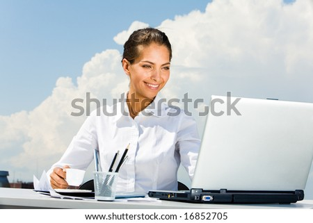 Portrait of pretty business lady holding a cup and looking at monitor of laptop