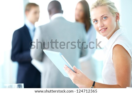 Portrait of pretty businesswoman with touchpad looking at camera in working environment