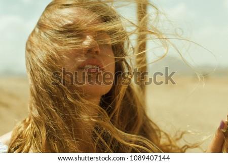 portrait of pretty caucasian girl with windy hair in desert