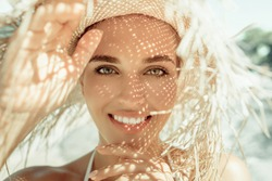 Portrait of pretty cheerful woman wearing straw hat in sunny warm weather day. Walking on the beach