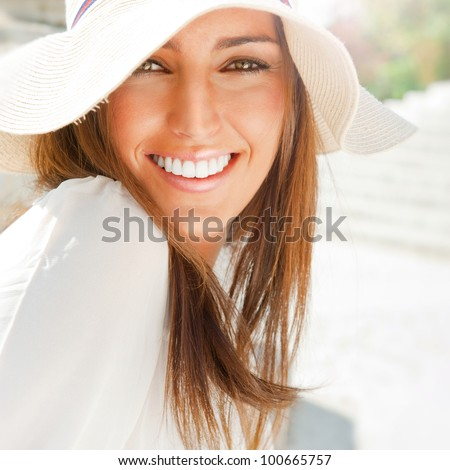 Portrait of pretty cheerful woman wearing white dress and straw hat in sunny warm weather day. Walking at summer park and smiling