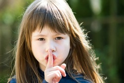 Portrait of pretty child girl with gray eyes and long hair holding point finger on her lips with hush sigh. Cute female kid on warm summer day outside.