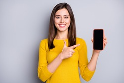 Portrait of pretty content cheerful girl holding in hand demonstrating gadget advert isolated over grey color background