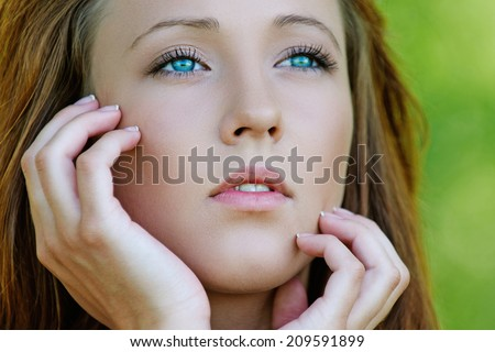 Portrait of pretty dark-haired pensive girl at summer green park.