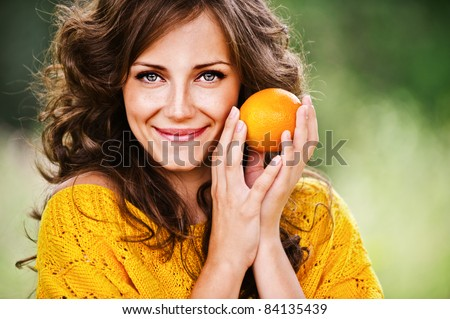 Portrait of pretty dark-haired woman holding juicy delicious orange at summer green park.