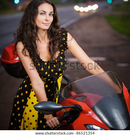 Portrait of pretty dark-haired young woman wearing dress, standing near red motorbike at road.