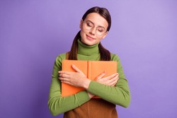 Portrait of pretty dreamy cheery girl embracing holding book diary isolated over bright violet color background