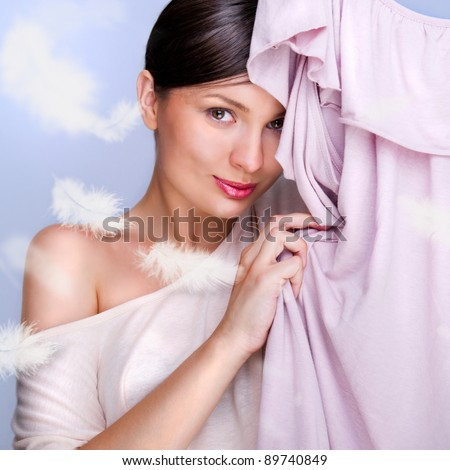 Portrait of pretty fashionable woman trying new clothes. Fashion poster shot indoors at studio. Lots of feathers around. Soft textile concept
