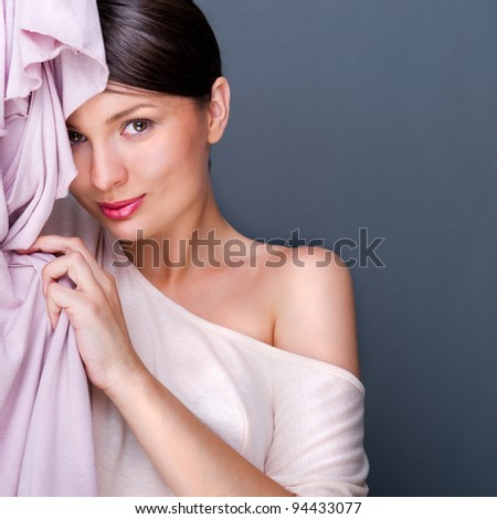 Portrait of pretty fashionable woman trying new clothes. Fashion poster shot indoors at studio against grey background.