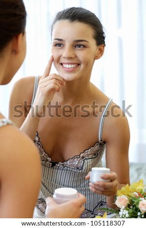 Portrait of pretty female applying cream onto her face and smiling