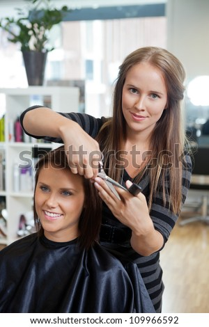 Portrait of pretty female beautician cutting hair of customer at parlor