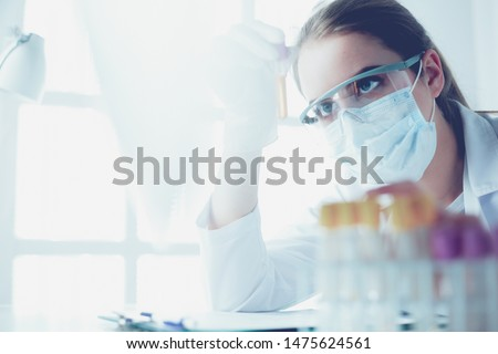 Portrait of pretty female laboratory assistant analyzing a blood sample at hospital #1475624561