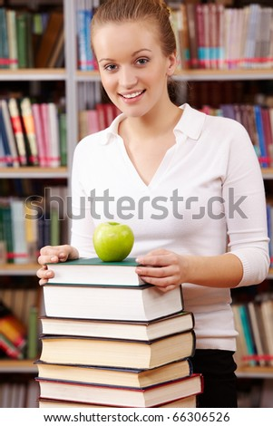 Portrait of pretty female looking at camera with green apple on top of book heap near by