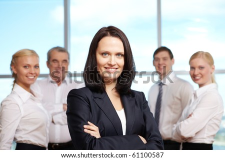 Portrait of pretty female looking at camera with group of colleagues on background