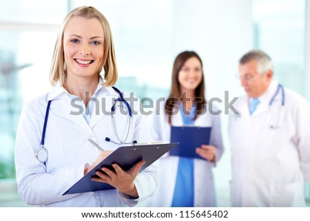 Portrait of pretty female practitioner looking at camera in working environment