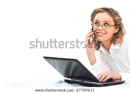 Portrait of pretty female speaking on cellular phone with laptop near by