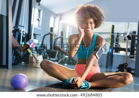 Portrait of pretty fit girl in sport clothes with balance ball in gym